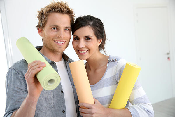 Portrait of smiling couple holding wallpaper rolls